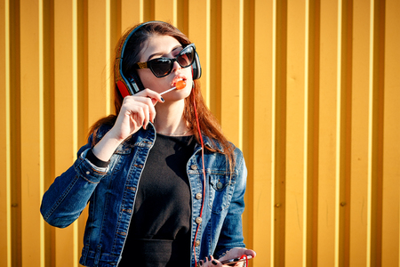 sucks: Cheerful stylish young girl in jeans jacket, headphones with phone, wearing sunglasses, listening to music by the yellow wall on sunny day and sucks candy on chupa chups stick. With space for text Stock Photo