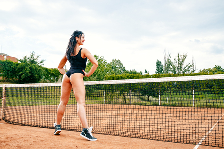 Beautiful young free sports sexy fitness girl dressed in bodysuit, sneakers, with a smart ass and long legs, on a sports ground on a tennis court with a beautiful sky in the background