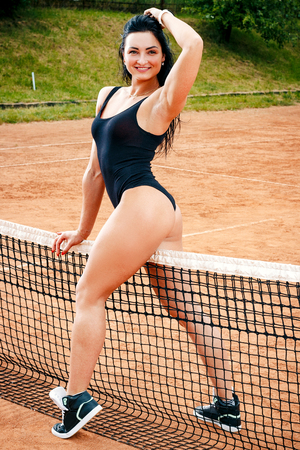 A beautiful young free sports girl dressed in bodysuit, sneakers and sunglasses, with a smart and long legs, on a sports field with a tennis net between her legs