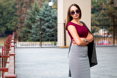 Beautiful girl or woman in a skirt and blouse, is confident and successful. Business lady, the concept of success and achievements, fashion and beauty