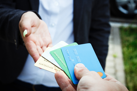 Concept of purchases, banking services. A woman in a suit and glasses takes several credit cards from a man. With a place for advertising text. Stock Photo