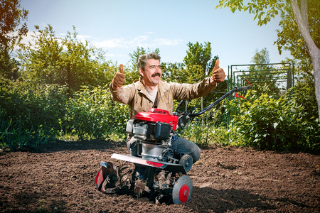 Happy man Farmer plows the land with a cultivator, preparing it for planting vegetables, on a sunny day garden