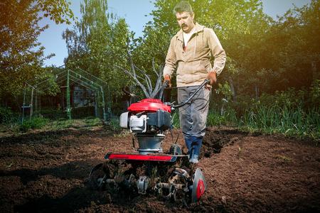 농부는 경작자와 함께 토지를 갈아서 화창한 날의 정원에서 채소를 준비합니다.