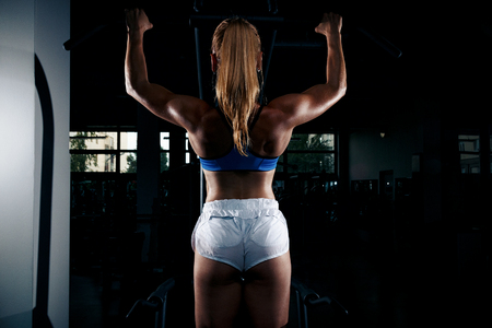 Fitness young sweaty girl with a sports body in the gym doing exercises for back pulling up on a horizontal bar Imagens