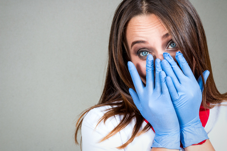 Vrouw of meisje verpleegkundige of arts in medische gewaad is geschokt en heeft betrekking op haar gezicht met steriele handschoenen op haar handen tegen een lichte achtergrond Stockfoto