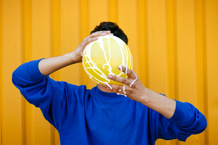 durty: Stylish serious guy in a blue sweater, with a yellow inflatable ball poured with a white liquid