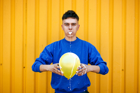 durty: Stylish serious guy in a blue sweater, with a yellow inflatable ball. Pouring out a white liquid from the mouth and a white liquid sprayed with a ball