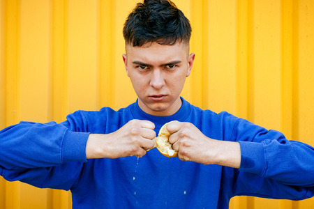 durty: Stylish serious guy in a blue sweater tears a lemon Stock Photo