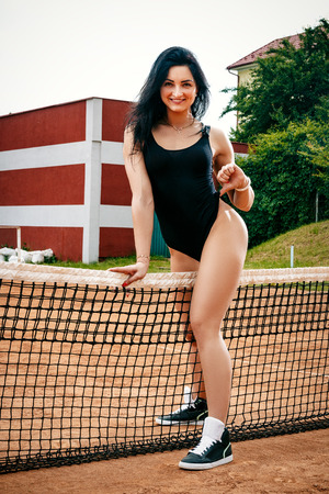 A beautiful young free sports sexy girl dressed in bodysuit, sneakers and sunglasses, with a smart ass and long legs, on a sports field with a tennis net between her legs Фото со стока