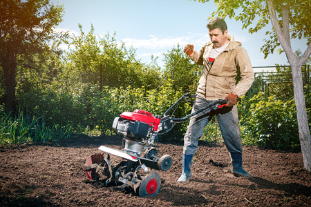 arando: Happy man Farmer plows the land with a cultivator, preparing it for planting vegetables, on a sunny day garden