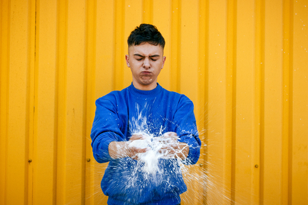 durty: A stylish serious guy in a blue sweater, and a splash of white liquid in his hands and a lot of spray