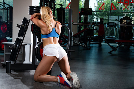 Fitness young sweaty girl with a sports body in the gym sexually stands in a doggy style pose while leaning on a sports equipment for the rods Stock Photo