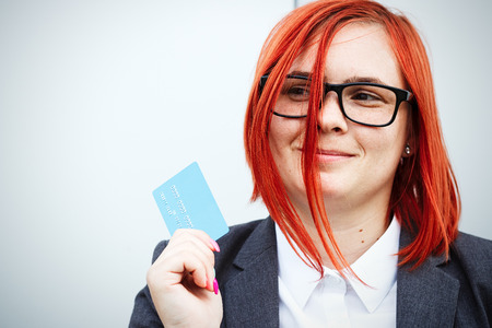 Concept of purchases, banking services. A woman in a suit and glasses shows a credit card. With a place for advertising text. Stock Photo