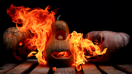 Two Very scary and dangerous Halloween pumpkins, with a terrible look and a grinning villain, in the dark on a wooden pallet, attack a good pumpkin, with tongues of flame spewing them from within