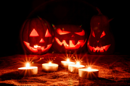 Several very scary Halloween pumpkins, with a menacing gaze and a grinning villain, glow from the inside and around them glow the candles located on the pedestal in the dark Stock Photo