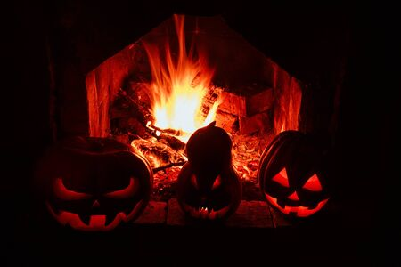 Halloween pumpkins formidable and funny, glow from within and around them flames flames located on the pedestal in the dark