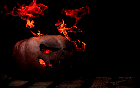 A very dangerous dangerous Halloween pumpkin, with a stern gaze and a smirk of a villain, in the darkness on a wooden pallet, spouts out the mouths and eyes of the flames of fire.