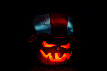 Very scary Halloween pumpkin, with a menacing glance and a grinning villain, in the dark with a football fans cap
