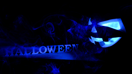 Halloween concept. An ominous pumpkin with Halloween inscription, with a cold blue glow and smoke, a poster for a party