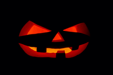 The concept of Halloween. The ghastly, ghastly pumpkin glows with a fiery yellow light. mystical jack lantern in the darkness, isolated on black