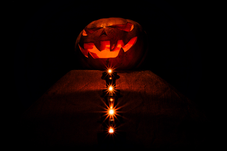 A very awful Halloween pumpkin, with a terrible look and a smirk of a villain, glow from within and around them glow the candles located on the pedestal in the dark