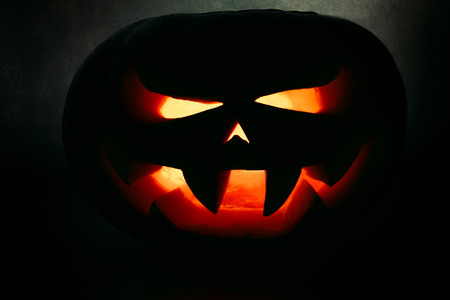 A very terrible Halloween pumpkin, with a terrible look and a smirk of a villain, in the dark Stock Photo