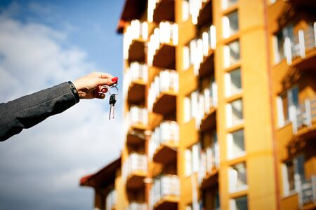 real estate sold: Concept of buying, selling and renting housing. A womans hand holds the keys to an apartment or a house, against a background of a residential house. With a place for advertising text.