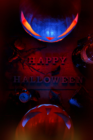 The concept of Halloween. two glowing orangery and blue light angry terrible pumpkin with a bat lamp, leaves and an alarm clock, a jack-lamp with an inscription of a happy Halloween, on a wooden background
