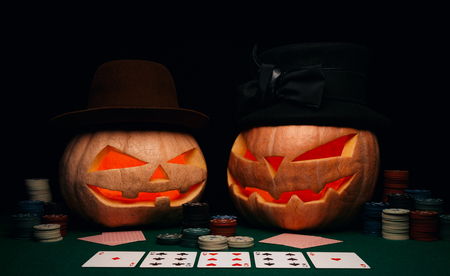 The concept of Halloween. Evil scary pumpkins play poker in hats. Jack Lantern among poker chips and cards