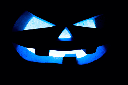 Halloween concept. Glowing with a icy blue light, a vicious, terrible pumpkin. mystical jack lantern in the darkness, isolated on black