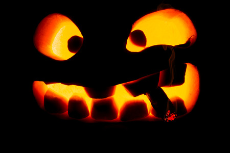 Halloween concept. The ghastly, ghastly pumpkin glows with a fiery yellow light with a smoking cigar. mystical jack lantern in the darkness, isolated on black