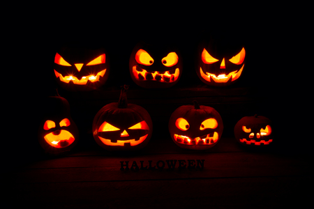 The concept of Halloween. A lot of Evil scary pumpkin in the dark. Jack Lantern in the darkness with Halloween inscription Stock Photo