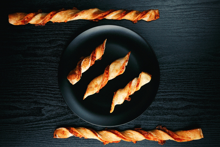tradition: Tasty appetizing cheese sticks on a black plate on a wooden black table