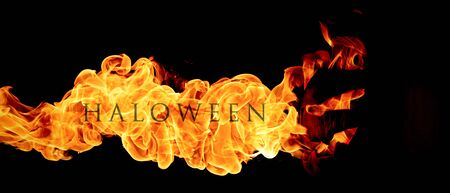 hellish: Halloween concept. The evil terrible pumpkin spews the hellish flames. Jack Lantern in dark with letters Halloween in fire Stock Photo