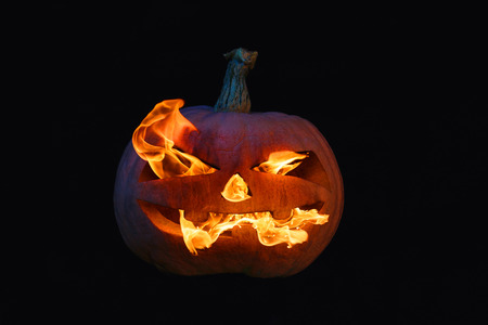 The concept of Halloween. The evil terrible pumpkin spews the hellish flames. Jack Lantern Stock Photo