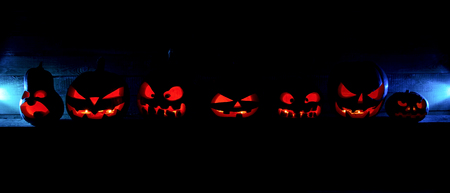 The concept of Halloween. Many glowing fiery light angry scary pumpkins. jack lantern in the dark, on a wooden background Stock Photo