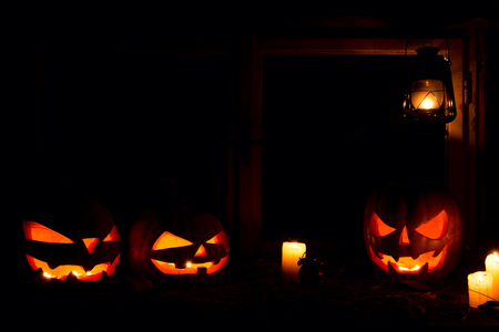 Halloween - pumpkins, candles and a lamp on leaves and logs, against the background of a window