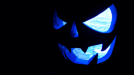 A very terrible Halloween pumpkin, with a terrible look and a smirk of a villain, in the dark with ice cold light