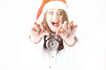 Christmas time. Beautiful woman plus size in Santa Claus hat holding alarm clock. New Year concept. Beautiful model xxl. Focus on the clock. Five minutes to twelve
