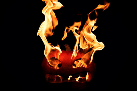 The concept of Halloween. The evil terrible pumpkin spews the hellish flames. Jack Lantern Stock Photo