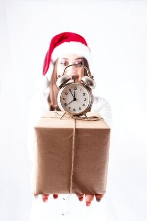 Happy cute fat Santa girl. Model in santa hat. XXL a woman celebrating Christmas and a new year. female is holding a present and small clock is an alarm clock. focus on the gift