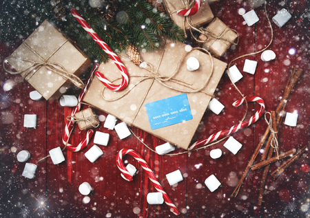 Christmas composition, new year concept, discounts, credit card and gifts. Boxes of surprises, candy staff, rope, Christmas tree branches, bumps, marshmelow on wooden mahogany background. with painted snow