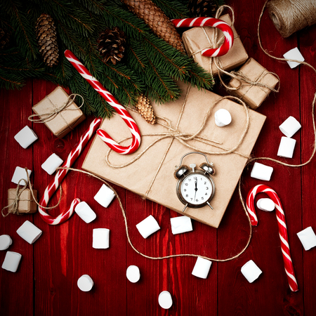Christmas composition, the concept of the new year. Boxes of surprises, candy staff, alarm clock, ropes, Christmas tree branches, bumps, marshmelow on a wooden mahogany background Stock Photo