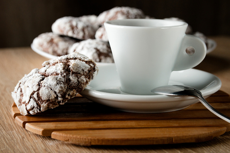 Delicious appetizing chocolate cookies cracked on a plate on a wooden table and a cup of coffee with space for text Stock Photo