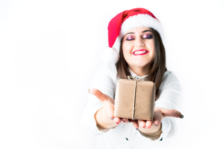 Christmas presents. Beautiful woman plus size in Santa Claus hat holding a gift in hands. New Year gifts. Beautiful model xxl. Focus on the gift