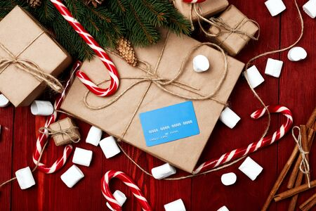 Christmas composition, new year concept, discounts, credit card and gifts. Boxes of surprises, candy staff, rope, Christmas tree branches, bumps, marshmelow on wooden mahogany background Stock Photo