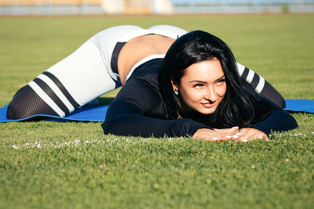 fitness girl on stadium, sporty women in sport suit, do exercises on sunny day. Sexy brunette with muscles body posing. female stretching on carpet and grass