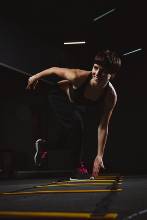 fitness girl doing crossfit exercises in gym in dark hall, sporty woman sexy in pose doing functional training, poster banner healthy lifestyle