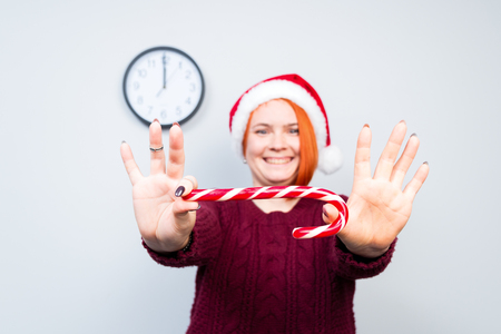 Christmas New Year happy woman in Santa Claus hat with candy sticks lollipop in hands