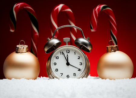 Christmas composition. Greeting card for new year clock alarm clock and toy balls candy stick on snow on red background with place for greeting text